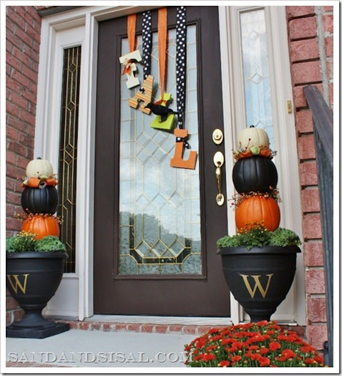 front porch with two pumpkin topiaries and fall door decor