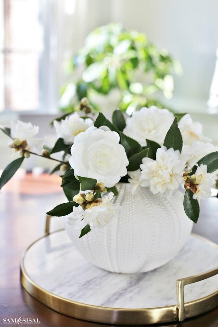 arrangement of white camellias in a white vase