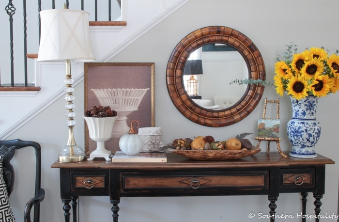 console table in foyer decorated for fall with round mirror above