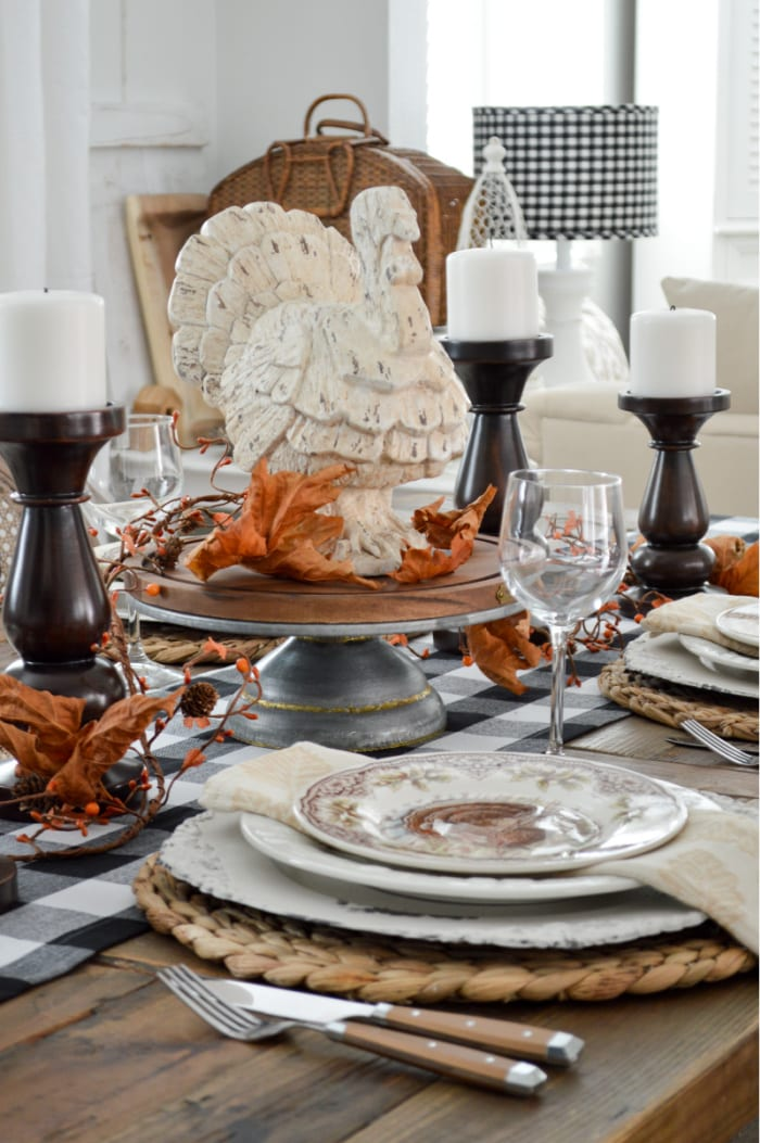 white turkey centerpiece on a table set for Thanksgiving