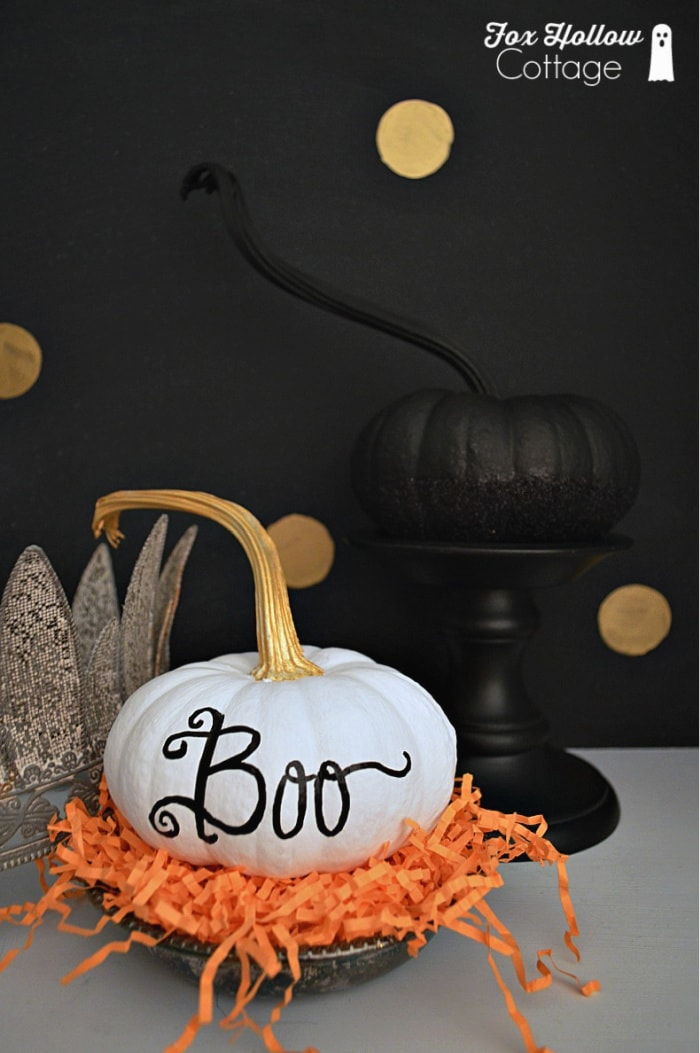 white pumpkin with the word boo painted on one side