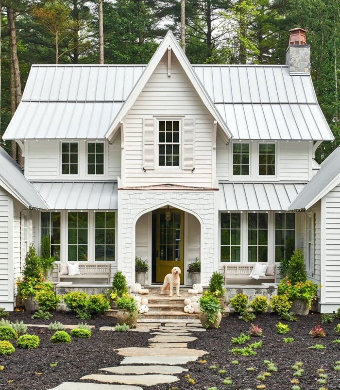 exterior of house with white siding and gray metal room