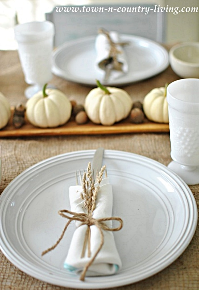 Thanksgiving table set with white dishes and a white pumpkin centerpiece
