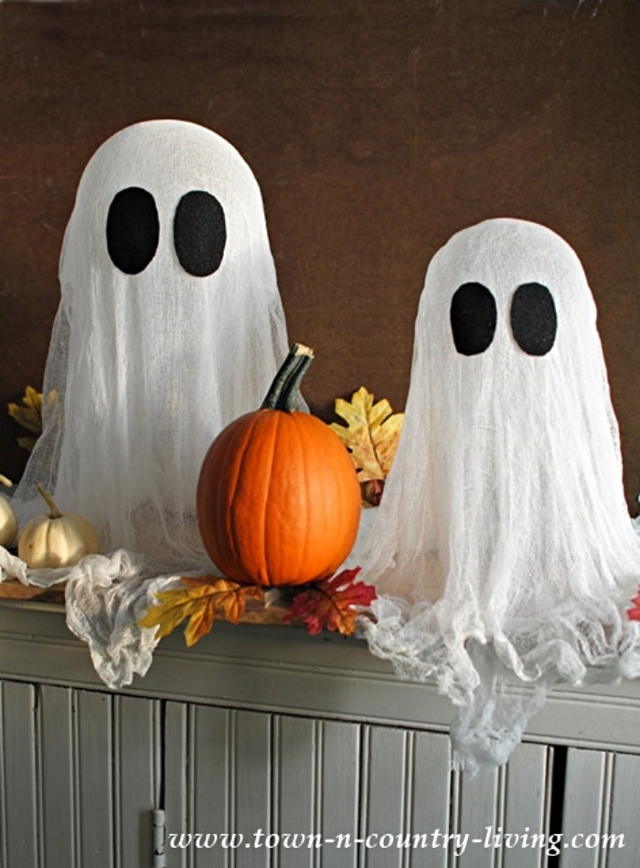 two small diy ghosts made with gauze and a pumpkin