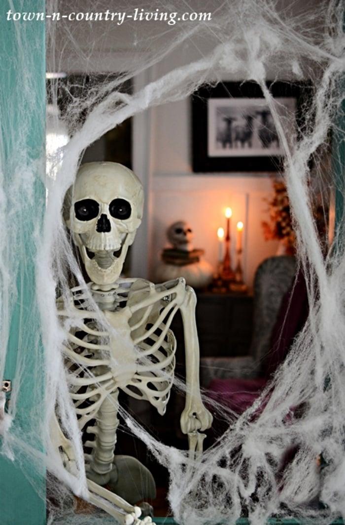 Fake skeleton in doorway with fake spider webs for Halloween
