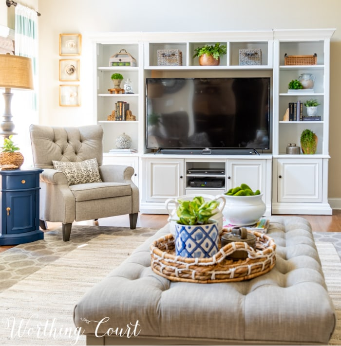 living room with white entertainment center, gray arm chair and gray coffee table