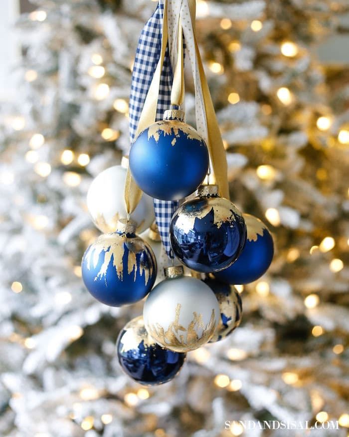 blue, white and gold Christmas ornaments in a bunch hanging by ribbon