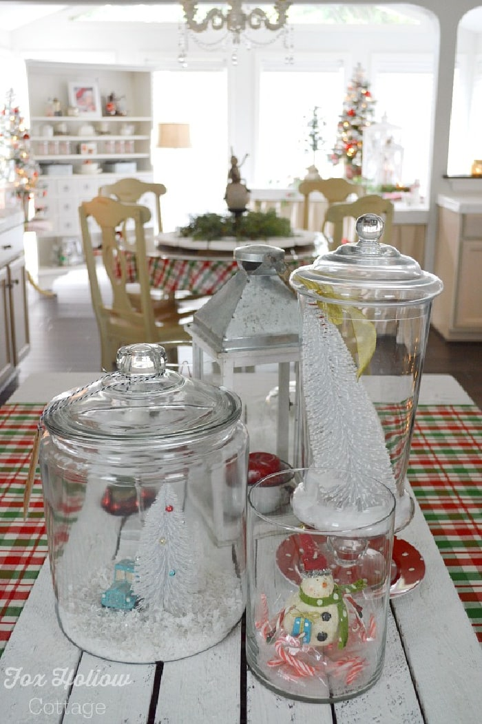 Glass cannisters with Christmas decor inside and dining area in the background