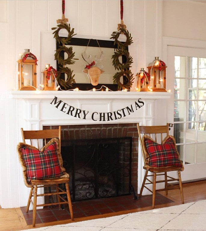 two chairs with pillows beside fireplace decorated for Christmas