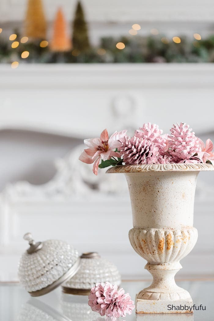 white urn filled with pink pinecones