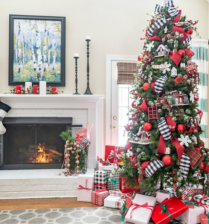 Decorated Christmas tree with gifts sitting beside fireplace