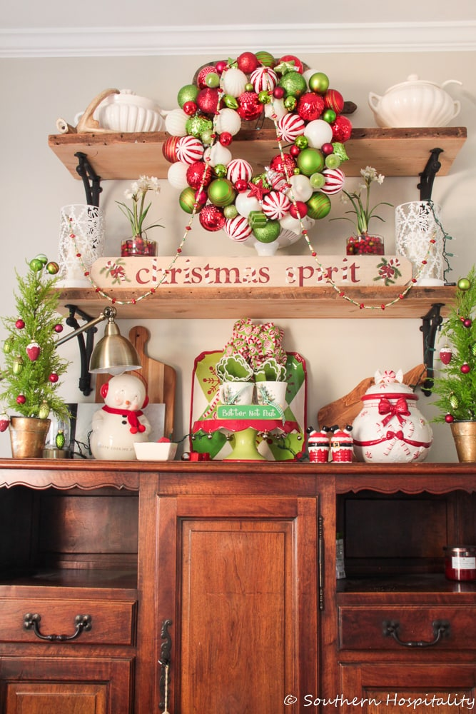 shelves above sideboard decorated with red and green Christmas decor