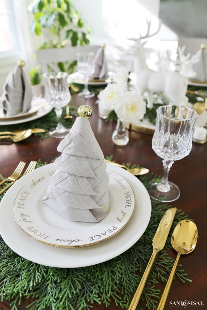gold and white table setting with napkin folded like a Christmas tree