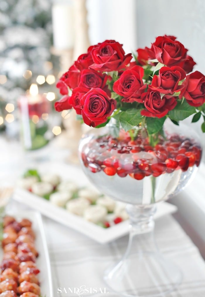 glass pedestal vase filled with red roses and cranberries floating in water
