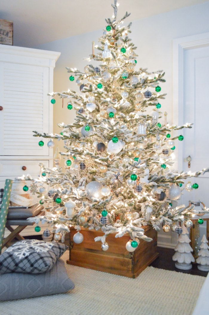 flocked Christmas tree with green and white ornaments
