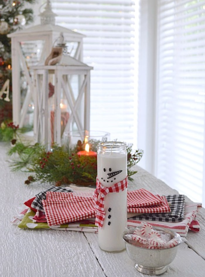 table display with white lanterns, linens and tall glass candle with snowman sticker face