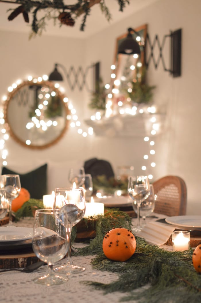 Christmas table with greenery, oranges and blurred Christmas lights in the background
