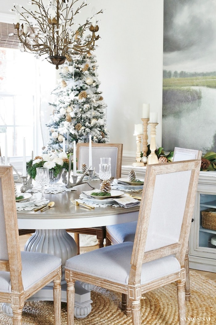 round dining room table set for Christmas with chairs and Christmas tree in background