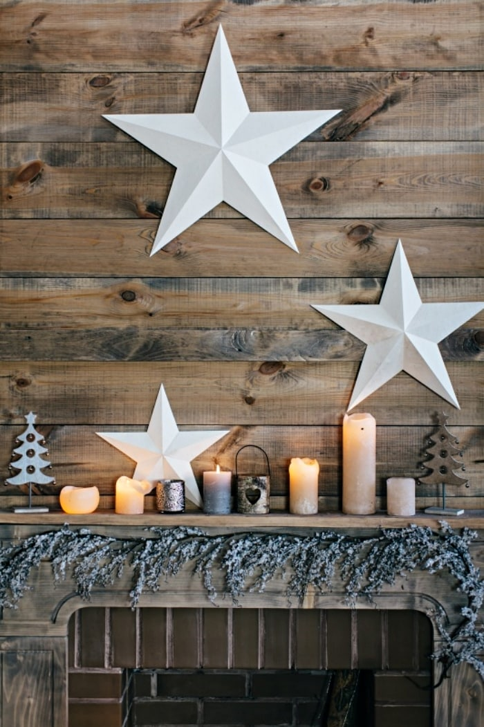 3 white stars hanging on wood planked wall above mantel