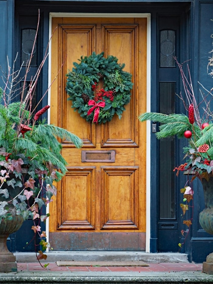 wood front door with evergreen Christmas wreath with a red bow