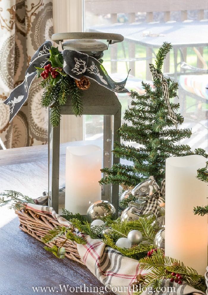 gray lantern with white candle and mini Christmas tree in a basket tray lined with a plaid scarf