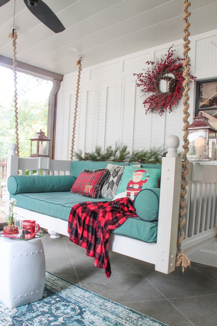 white wood porch swing hanging from ceiling with rope with teal cushions