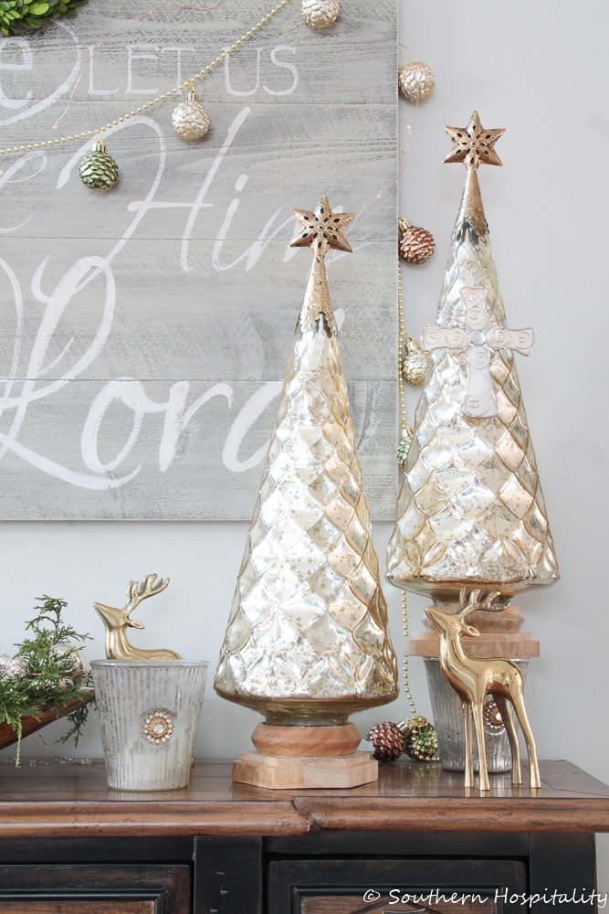 pair of mercury glass Christmas trees and gold deer displayed on a table