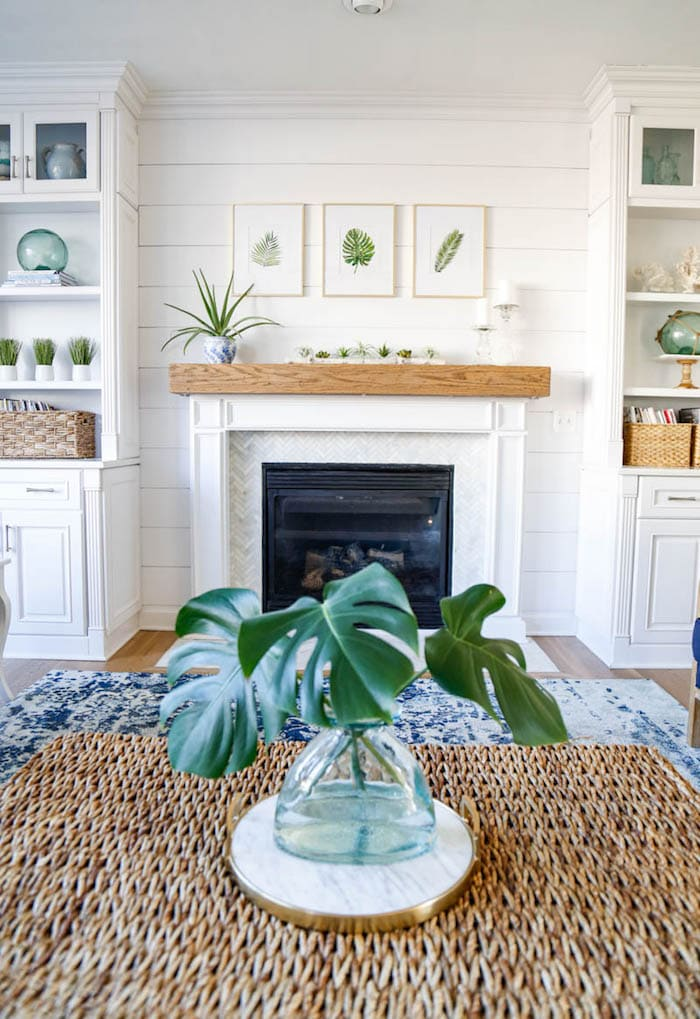 white fireplace flanked by white bookcases with decorations