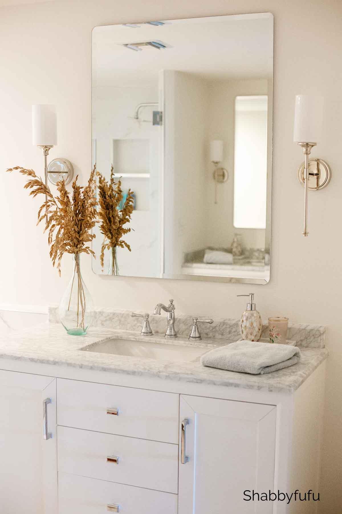 white freestanding bathroom vanity with carrara marble top