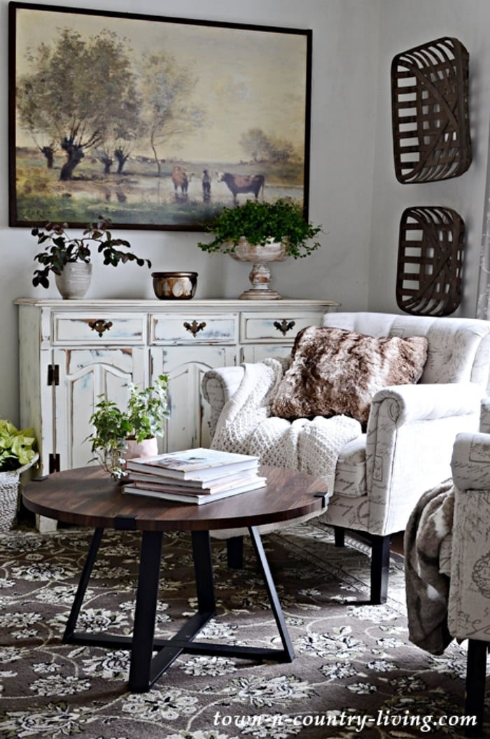 living room corner with accent chair, distressed white cabinet, large artwork and accessories