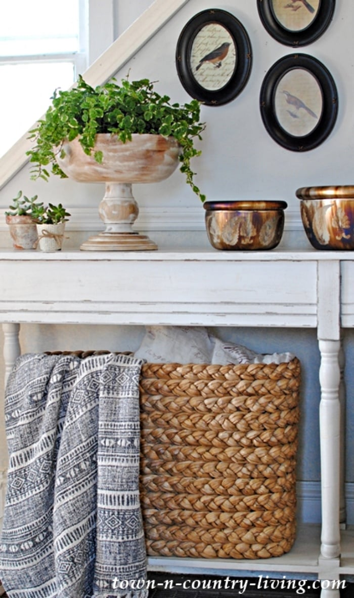 white console table style with distressed pedestal bowl, copper containers and large basket holding a blanket