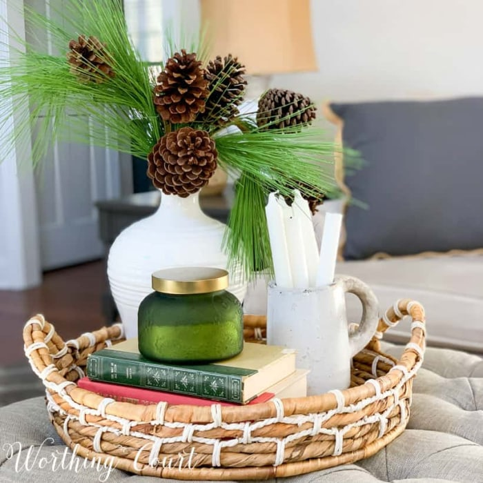 winter vignette on a coffee table in a round basket tray using green and white