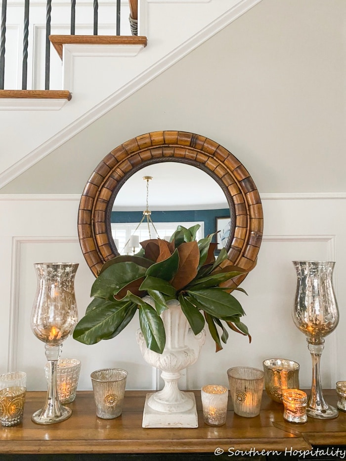 round mirror hanging on wall above console table filled with different types of candleholders and an urn with green leaves