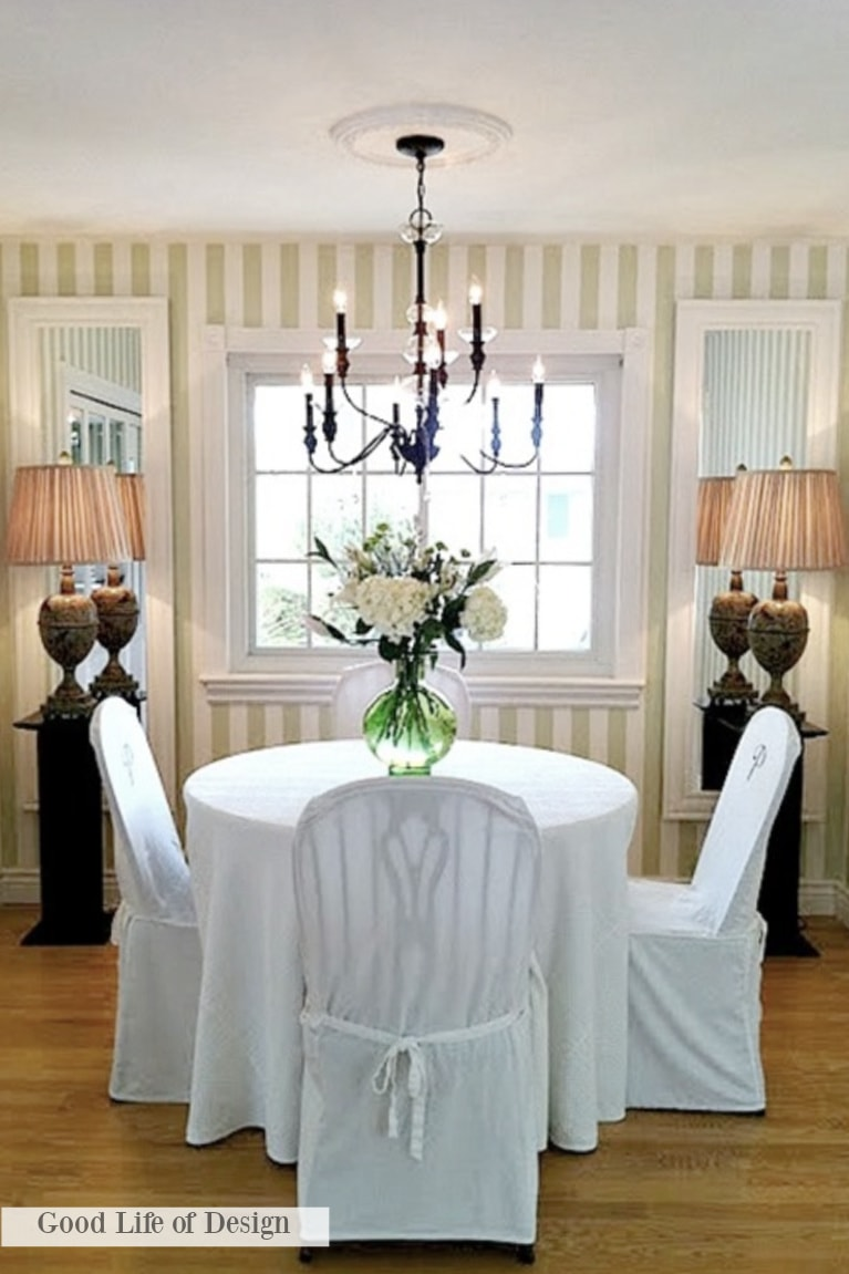 Charming Grandmillennial style in a dining room with preppy green stripe wallpaper and slipcovered dining chairs - Good Life of Design.