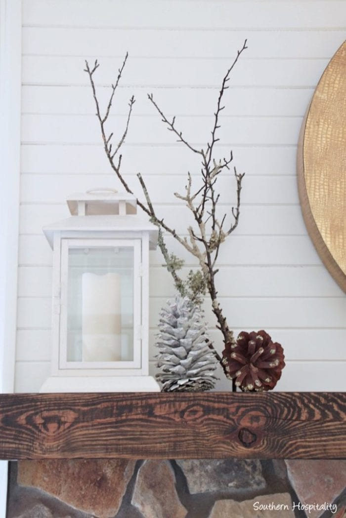 end of a mantel styled for winter with white lantern, pine cones and bare branches
