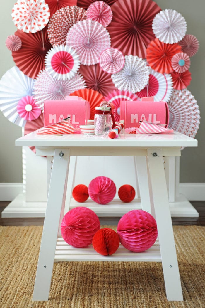 white table topped with red, pink and white fans on the wall for Valentine's Day