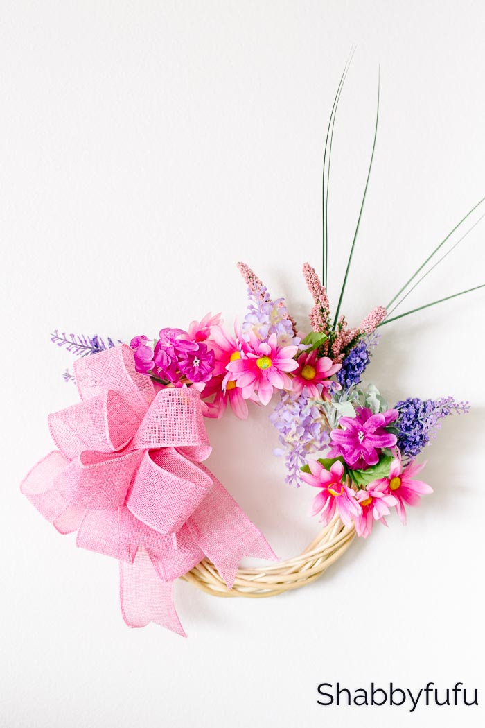 wreath made with pink and purple flowers with a pink bow