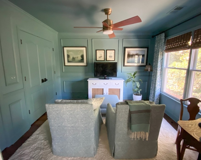 walls painted blue with picture frame molding in a sitting room with two chairs and a tv