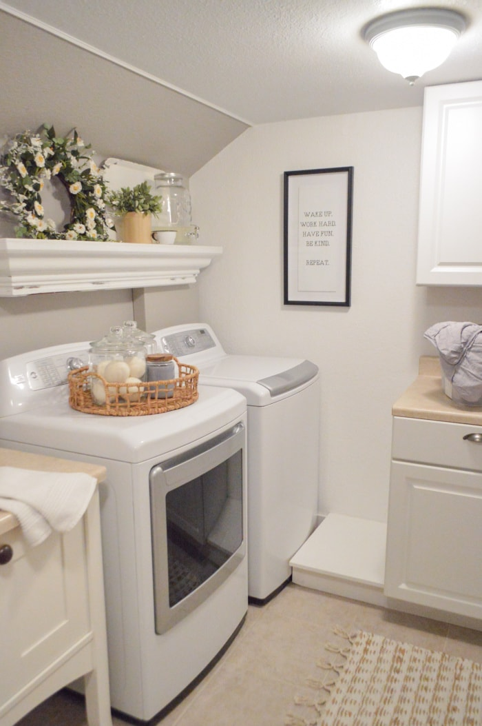 white washer and dryer in the corner of a laundry room with a shelf above