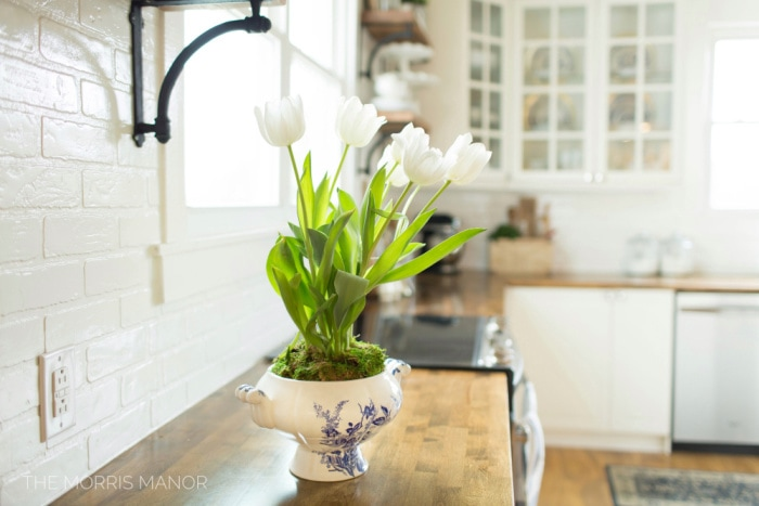 vintage container holding white tulips sitting on a kitchen counter