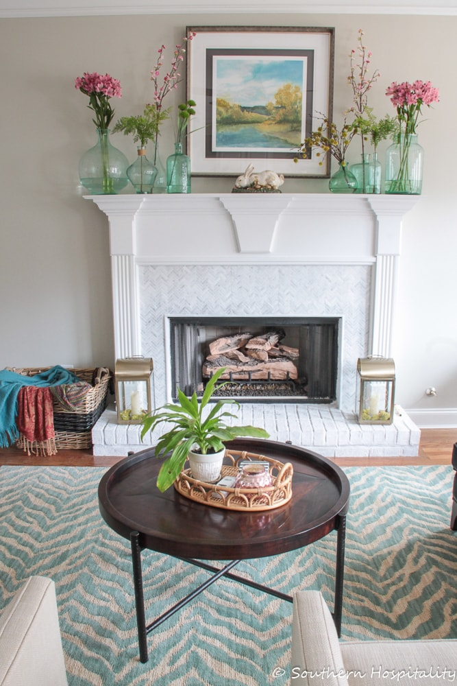 fireplace mantel decorated for spring with aqua glass demijohn bottles and pink flowers