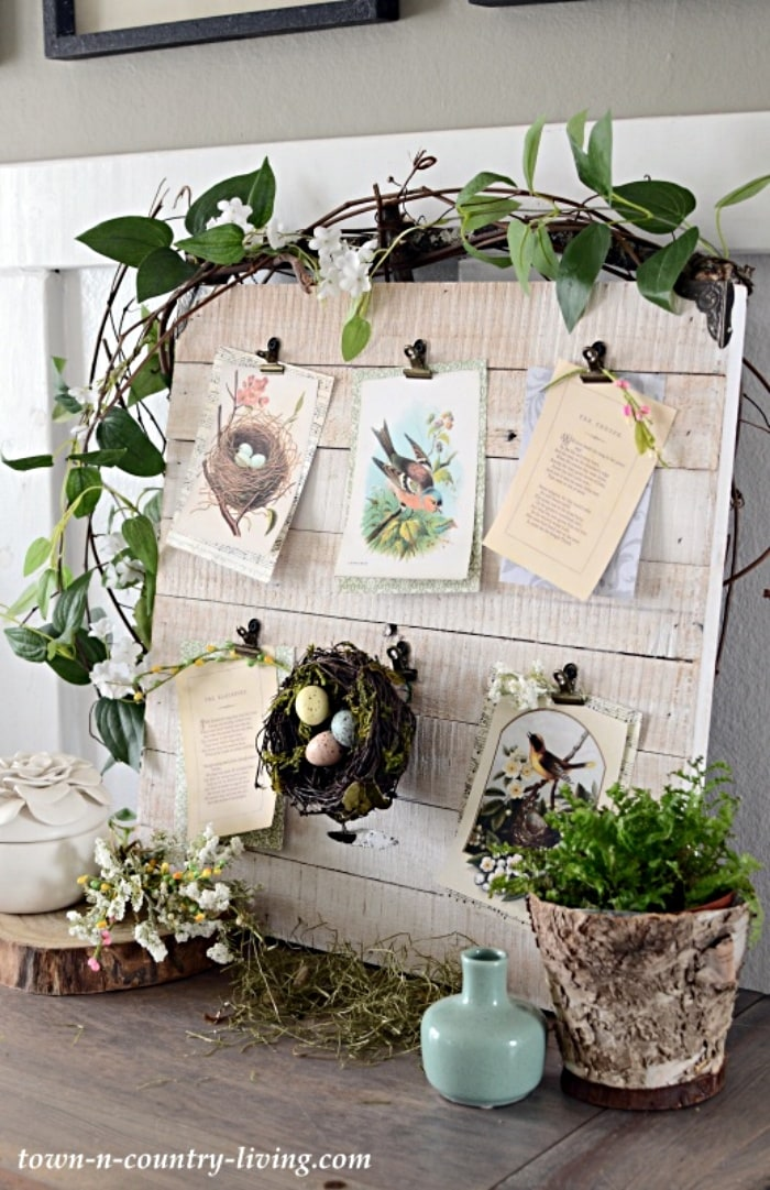 piece of painted wood with Easter cards and a birds nest attached to it for a spring display