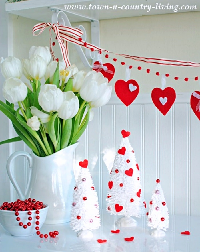 Valentine's vignette with white tulips, white bottle brush trees and a heart garland