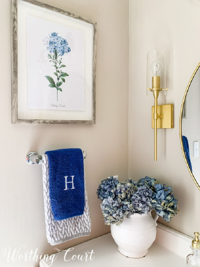 bathroom vanity styling with artwork, hand towels and blue hydrangeas in a vase