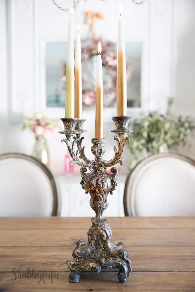 ornate silver candelabra with candles sitting on a dining room table