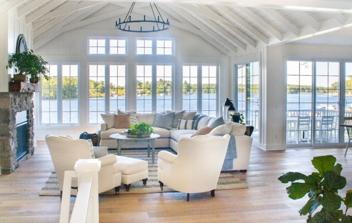living room with coastal decor and lots of windows overlooking a lake