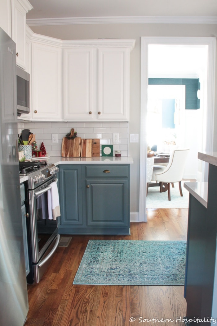 corner of kitchen with blue lower cabinets and white upper cabinets