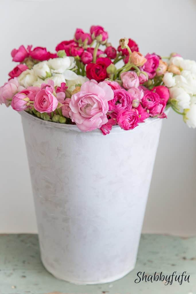 white bucket filled with pink, white and red flowers