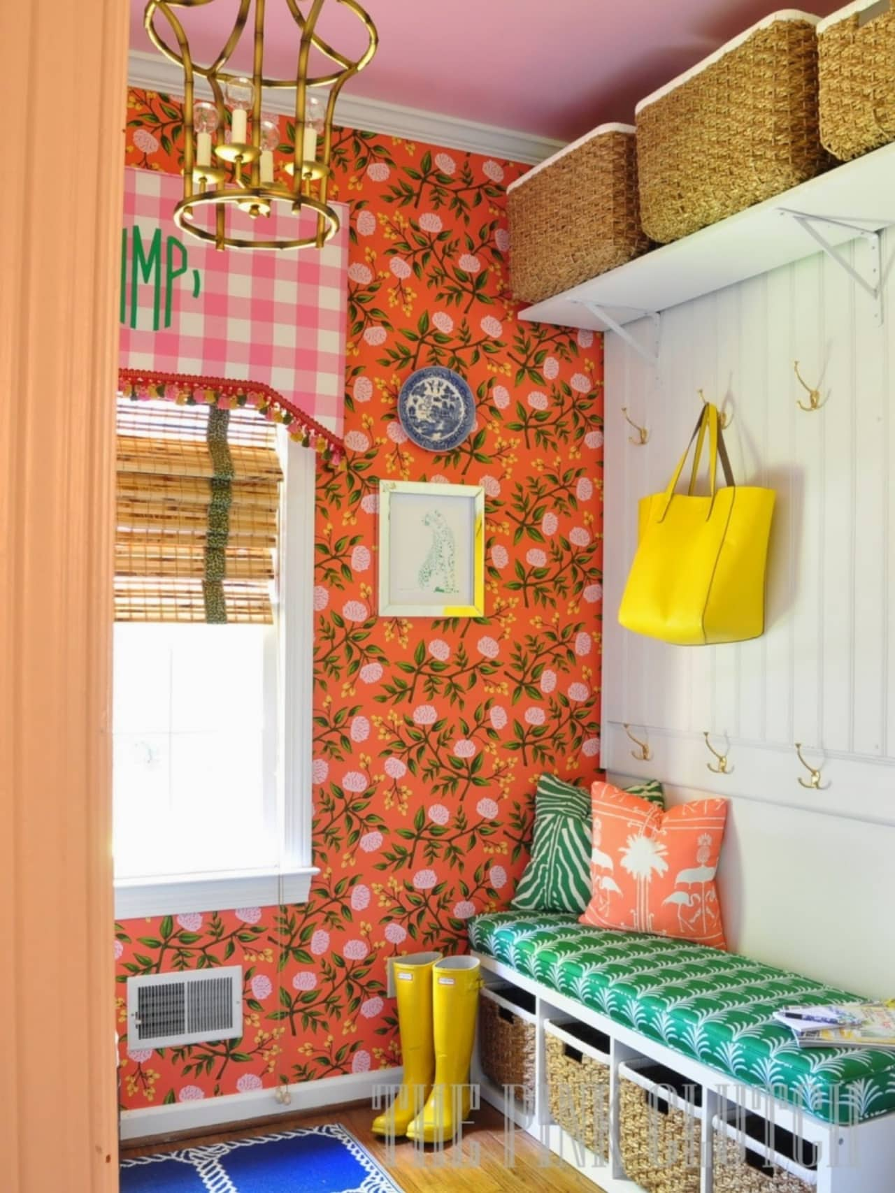 a very colorful mudroom with bench, hooks and a shelf with baskets