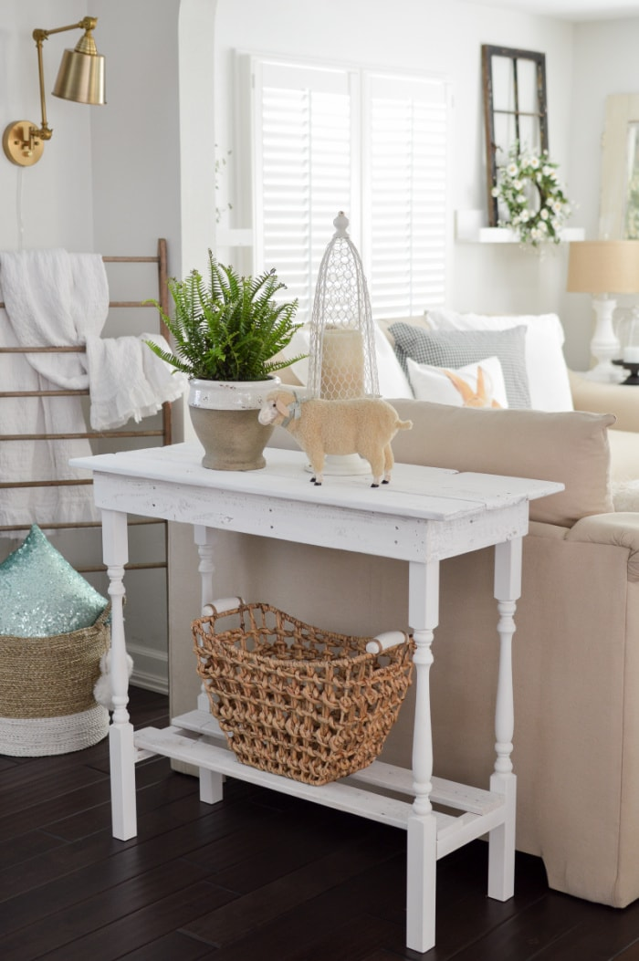 white sofa table with a spring arrangement against the back of a neutral sofa